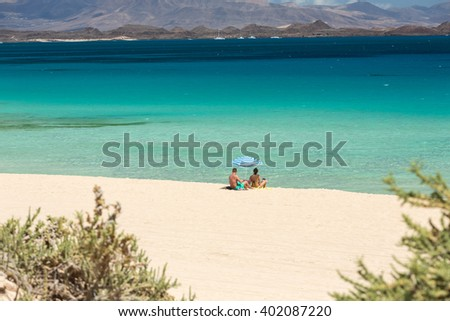 Tourists rest on Corralejo Beach on Fuerteventura, Canary Islands - stock photo