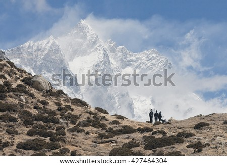 Tourists rest on the pass above the village of Dingboche. In the background is one of the highest peaks of the World Lhotse (8516 m) - Nepal, Himalayas. - stock photo
