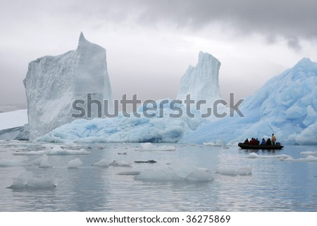 Tourists sailing between huge icebergs in Napassorsuaq Fjord, Greenland