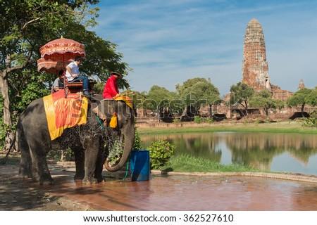 Tourists sightseeing Ayutthaya Historical park by sit on decoration elephant, Ayutthaya, Thailand - stock photo
