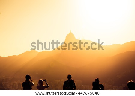 tourists silhouettes on a Pao do Asucar viewpoint with the Rio panorama at the background at the sunset time - stock photo