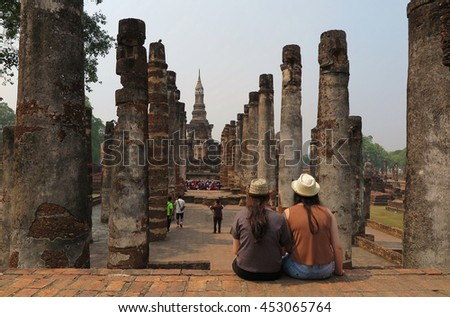 Tourists sitting before ruined columns & enjoying the majestic view of Wat Mahathat, an ancient Buddhist temple in Sukhothai Historical Park, Thailand ~ A beautiful UNESCO heritage site in Thailand - stock photo
