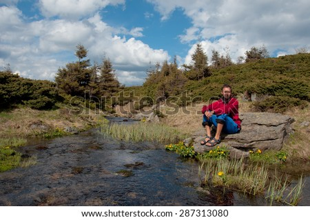 Tourists sitting on the bank of the beautiful river in the forest