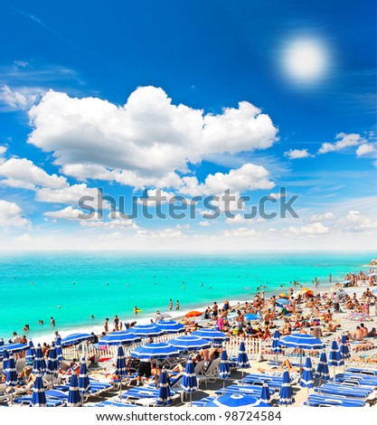tourists, sunbeds and umbrellas on summer hot day. mediterranean sea. beach in Nice, France, near the Promenade des Anglais - stock photo