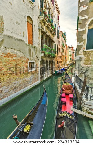Tourists travel on gondolas at canal Venice, Italy . Gondola trip is the most popular touristic activity in Venice. - stock photo