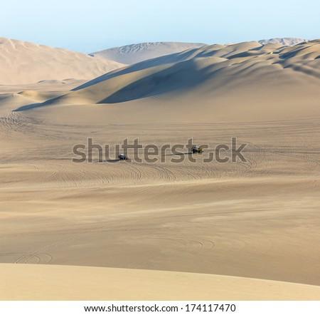 Tourists travel through the dunes in the Atacama Desert - Oasis of Huacachina, Peru, South America - stock photo