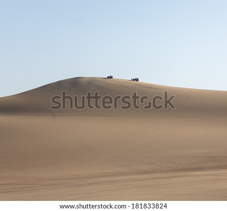 Tourists travel through the dunes in the atacama desert oasis of