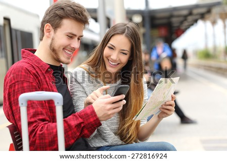 Tourists travelers consulting gps and guide from a smart phone in a train station - stock photo