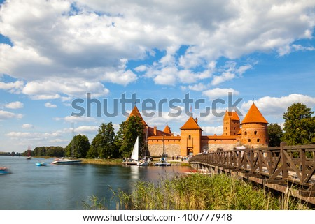 Tourists visit Trakai castle in sunny summer day, nice time to have boat trip. Long exposure, motion blur