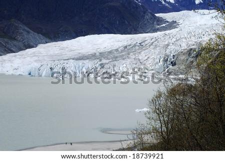 Tourists walking along beautiful Mendenhall Glacier in Juneau, Alaska. - stock photo