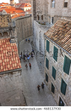 Tourists walking on the old streets in Dubrovnik, Croatia. Narrow streets of stones seem very nice. Green louver shutters on the windows of the houses.