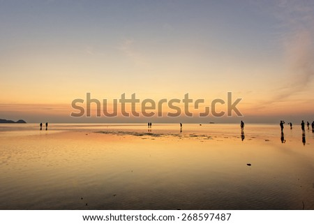 Tourists walking on water at sunset - Thailand