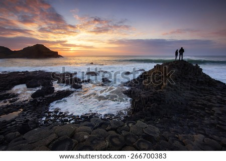 Tourists watching a sunset at the Giant's Causeway