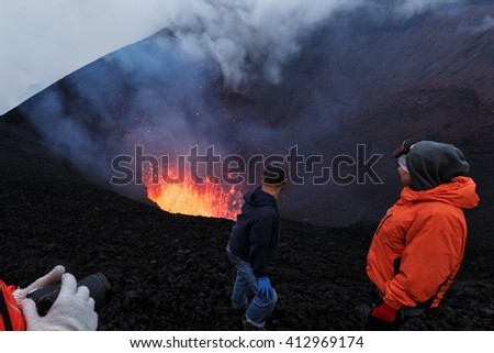 Tourists watching beautiful volcanic eruption, standing on slope of dangerous cinder cone of active volcano. Erupting Tolbachik Volcano (Klyuchevskaya Group of Volcanoes). Russian Far East, Kamchatka.