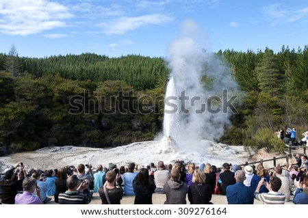 Tourists watching Erupting Lady Knox geysir in Wai-o-Tapu, Rotorua, New Zealand - stock photo