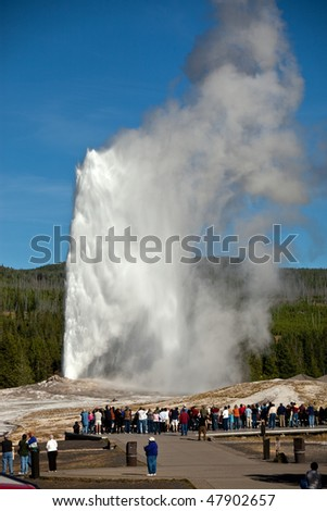 Tourists watching the Old Faithful eruption in Yellowstone National Park - stock photo