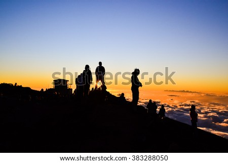 Tourists watching the spectacular sunset on the summit of Haleakala Crater (10,023 ft) on the island of Maui, Hawaii. Sun shining through the legs of a spectator. Observatories in the background. - stock photo
