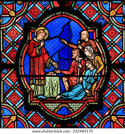 TOURS, FRANCE - AUGUST 14, 2014: Stained glass window depicting a Saint handing out bread in the Cathedral of Tours, France. - stock photo