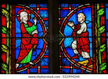 TOURS, FRANCE - AUGUST 14, 2014: Stained glass window depicting Jesus and a Believer in the Cathedral of Tours, France. - stock photo
