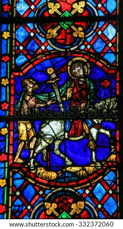 TOURS, FRANCE - AUGUST 14, 2014: Stained glass window depicting Saint Martin of Tours cuting a piece of his cloak for a beggar in the Cathedral of Tours, France.