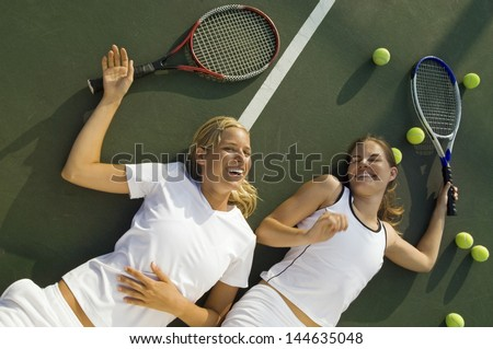 Tov view of two tired and happy women with racquets and balls lying on tennis court