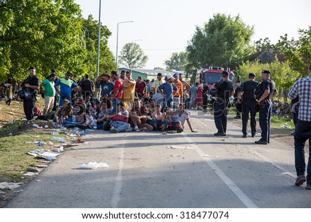 TOVARNIK, CROATIA - SEPTEMBER 18: Police guard the tip of the waiting line of Refugees on September 18, 2015 in Tovarnik, Croatia. 