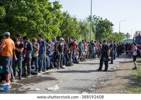 TOVARNIK, CROATIA - SEPTEMBER 18: Police guards the waiting line of Refugees on September 18, 2015 in Tovarnik, Croatia. 