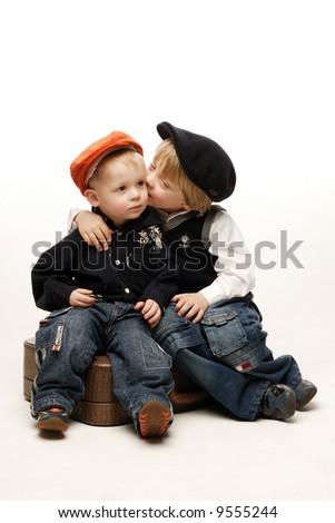 Tow boys sitting on suitcase kissing