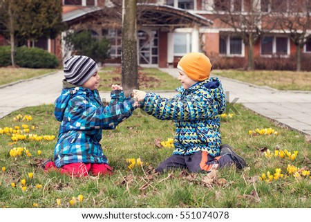Tow children boys sitting on grass with crocus flowers in front of a school or residential building and playing together.