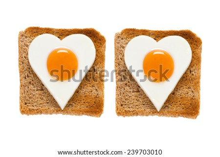 tow heart shaped cooked eggs on toast - stock photo