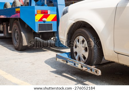 Tow truck towing a broken down car - stock photo