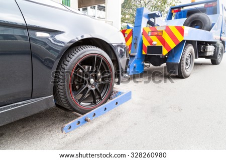 Tow truck towing a broken down car on the street. - stock photo