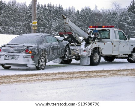 tow truck towing wrecked car in winter