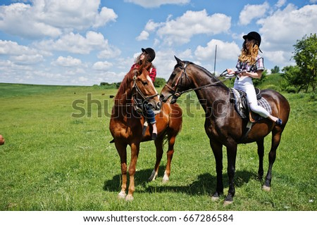 Tow young pretty girls riding a horses on a field at sunny day.
