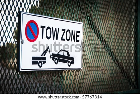 Tow Zone sign on a steel grid gate - stock photo