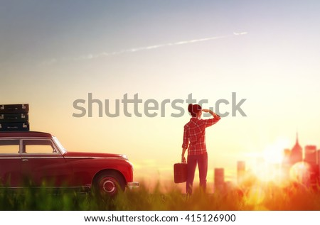 Toward adventure! Girl relaxing and enjoying road trip. Beautiful young woman looking on city. - stock photo