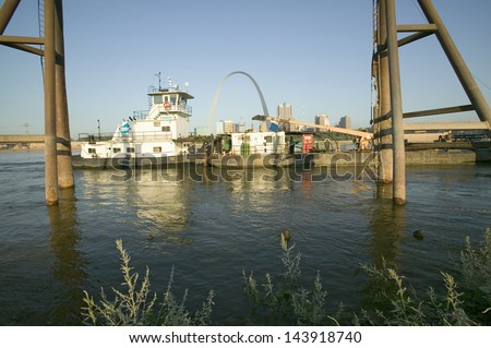 Towboat pushing barge down Mississippi River in front of Gateway Arch and skyline of St. Louis, Missouri as seen from East St. Louis, Illinois on the Mississippi River - stock photo