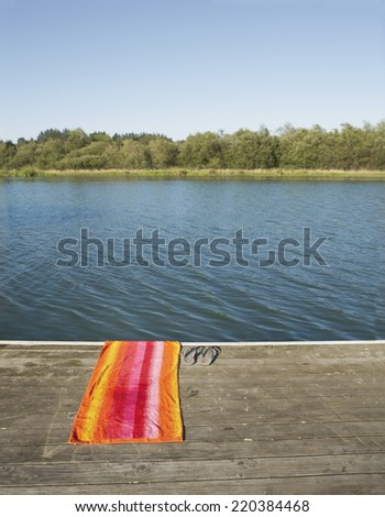 Towel and flip-flops by lake - stock photo