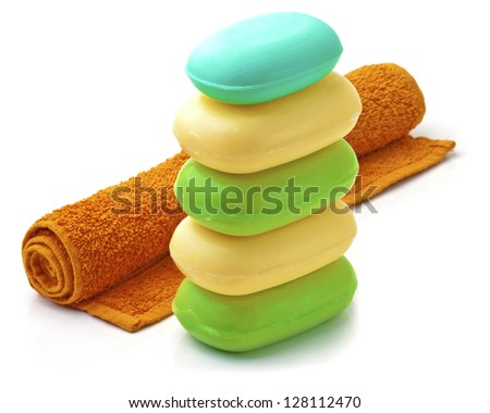 Towel and Stack of new colorful Soap Bars on white background. - stock photo