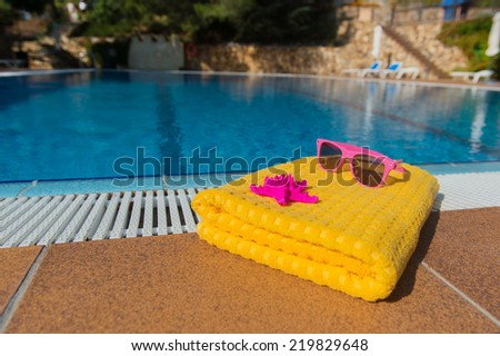 Towel and sunglasses at luxury outdoor swimming pool - stock photo
