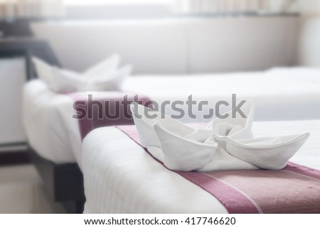 towel flower on bed in hotel. - stock photo