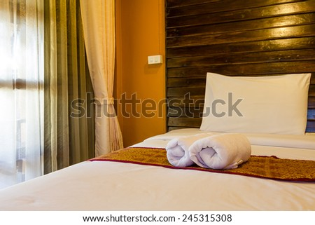 Towel in Hotel Room, Bedroom ready for guests in soft warm lighting - stock photo