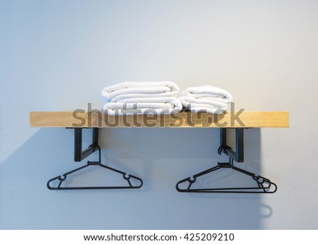 towel prepared on wood shelf and hanger. - stock photo