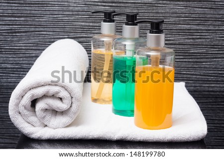 towel roll and pump bottles. - stock photo