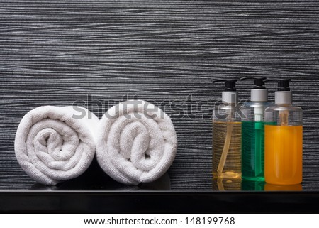 towel rolls and pump bottles. - stock photo