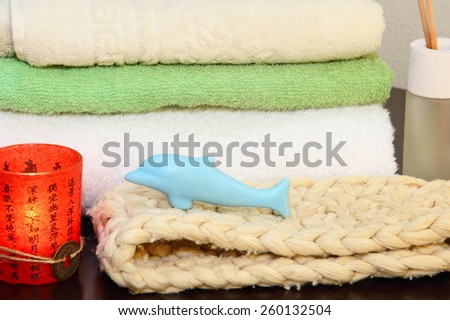 Towel stack, bast and soap in the form of a dolphin. - stock photo