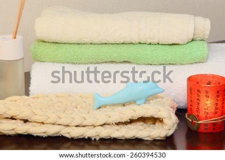 Towel stack, bast and soap in the form of a dolphin taken closeup. - stock photo