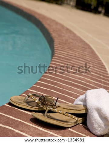 Towel, sun glasses and worn flip-flops laying beside a pool - stock photo