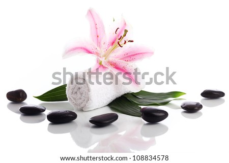 Towel with lily flower and stones for massage over white background