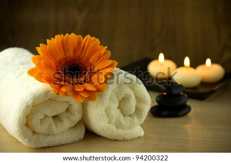 Towels and orange flower, candles and massage Stones in a Zen Spa. - stock photo